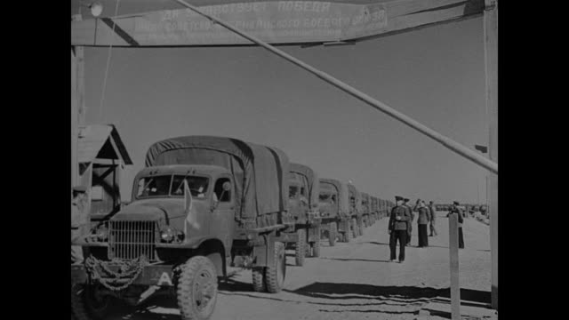 '1946' Superimposed over Russian officer and truck drivers / Russian USSR Soldier talking w/ Soviet officer truck convoy BG / Drivers getting into...