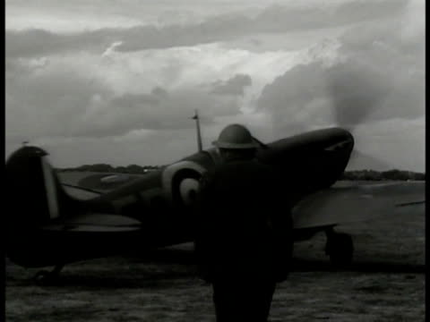supermarine spitfire airplane flying. spitfire turning on field pilots running. pilot & officer leaning on wing talking. crashed german airplane iron... - ナチスかぎ十字点の映像素材/bロール
