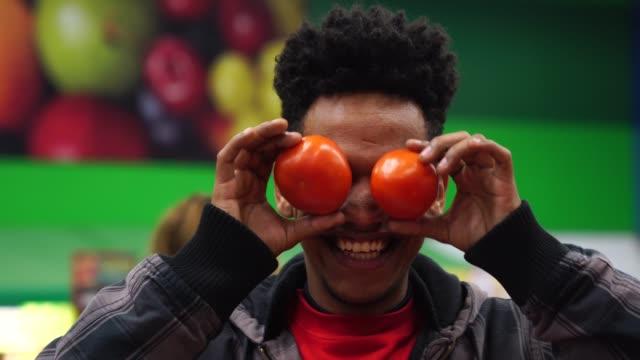 Supermarket Customer Having Fun with tomatoes
