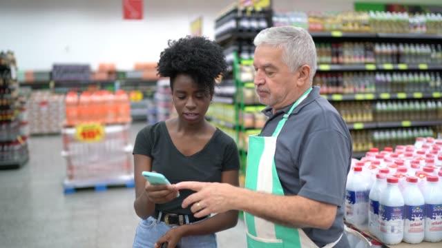vídeos de stock, filmes e b-roll de empregado do supermercado que ajuda um cliente a comprar - customer