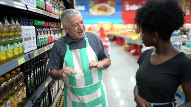 vidéos et rushes de employé de supermarché aidant un client à acheter - demander