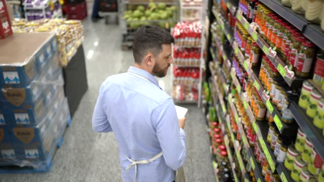 supermarket employee or owner walking and using digital tablet - non us location stock videos & royalty-free footage
