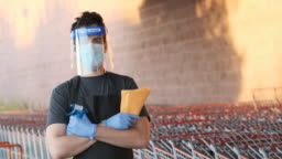 Supermarket employee wearing masks and latex gloves and disinfection products due contagion prevention