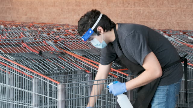 supermarket employee wearing masks and latex gloves disinfecting shopping carts due contagion prevention - career stock videos & royalty-free footage