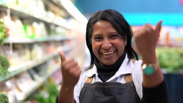 supermarkt mitarbeiter frau winkte - laden kunden zu kommen - heranlocken stock-videos und b-roll-filmmaterial