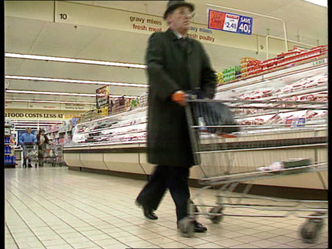 vídeos de stock e filmes b-roll de lms shoppers along in sainsbury's supermarket lams man pushing trolley along ms woman takes product from shelf cms tins of coca cola on shelf track... - sainsburys