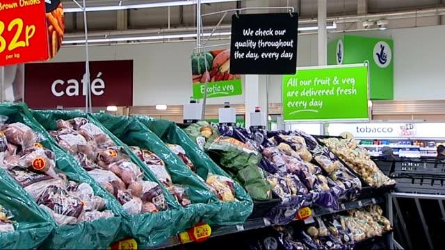 ASDA supermarket scenes Shoppers in vegetable aisle/ man selecting bananas/ potatoes on display/ apples on display/ bags of ready chopped vegetables...