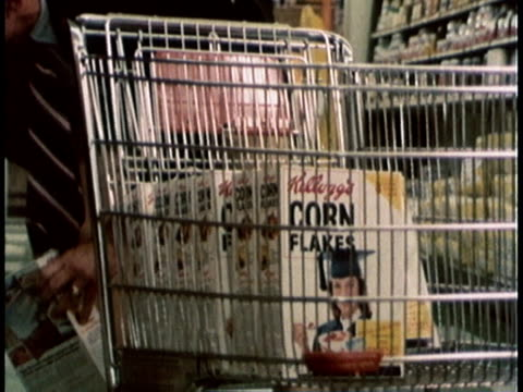 stockvideo's en b-roll-footage met 1978 montage a supermarket shopper filling basket with cereal boxes and a cashier pushing buttons on cash register / united states - kruidenier