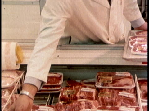1978 MONTAGE A supermarket worker handling packages of meat / United States