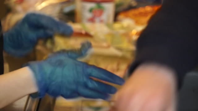 a supermarket worker wearing protective gloves to protect against coronavirus - checkout stock videos & royalty-free footage