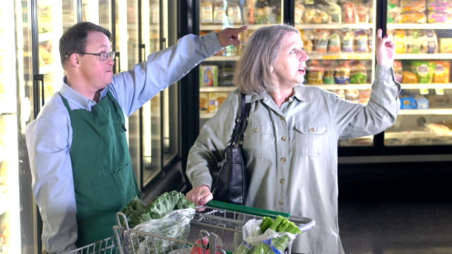 supermarket worker with down syndrome helps customer - learning disability services stock videos & royalty-free footage