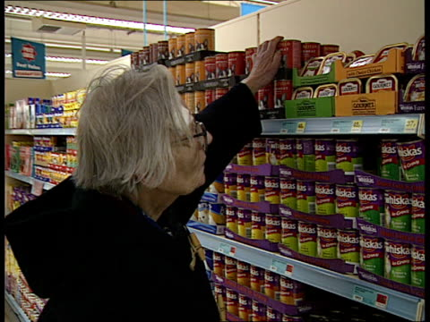 vídeos y material grabado en eventos de stock de supermarkets and the weather ltn woman feeding cat in kitchen and cat eating people at checkouts and shopping in supermarket woman buying cat food... - itv