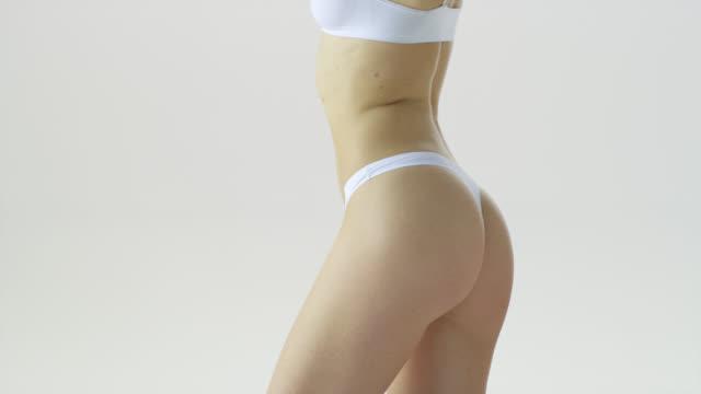 supermodels körperteile in weißer unterwäsche: oberschenkel, hüften, hintern, taille, brust. mode-video. erfasst in 7k r3d rot helium. 4k prores 4444. - hüfte stock-videos und b-roll-filmmaterial