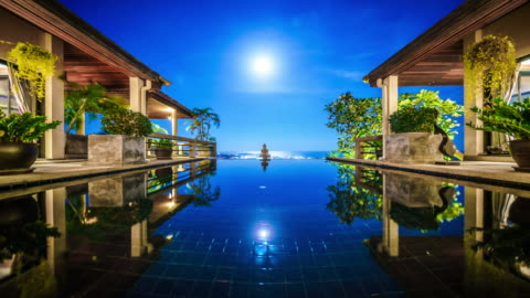 supermoon rising over the pool at the villa time lapse 4k - changing form stock videos & royalty-free footage