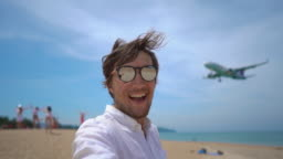 Superslowmotion shot of a happy tourist have fun on a tropical beach with an airplane flying over him