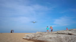 Superslowmotion shot of a tropical beach where airplanes fly over tourists heads before land in an airport