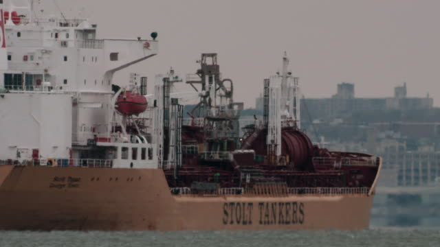 a supertanker sits off the port of bayonne shot with a telephoto lens on a grey day - tanken stock-videos und b-roll-filmmaterial