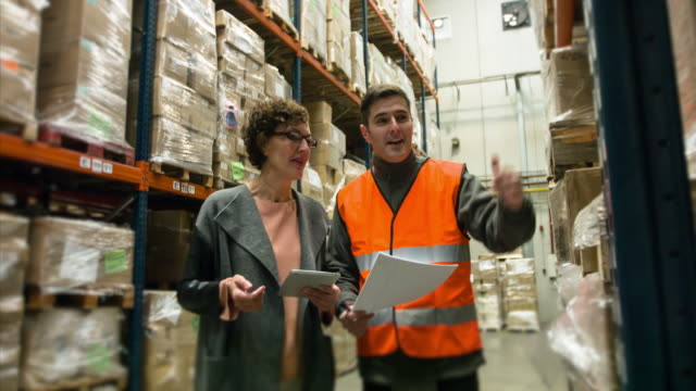 supervisor and worker with digital tablet talking in distribution warehouse - occupational safety and health stock videos and b-roll footage