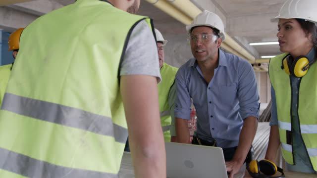 supervisor auf einer baustelle begrüßt ein neues mitglied zu seinem team während eines treffens auf einer baustelle - schutzbrille stock-videos und b-roll-filmmaterial