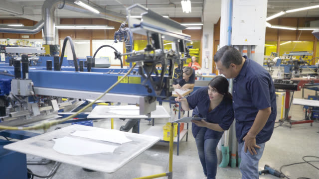 vídeos de stock e filmes b-roll de supervisor checking a machine with operator and pointing at parts - textile