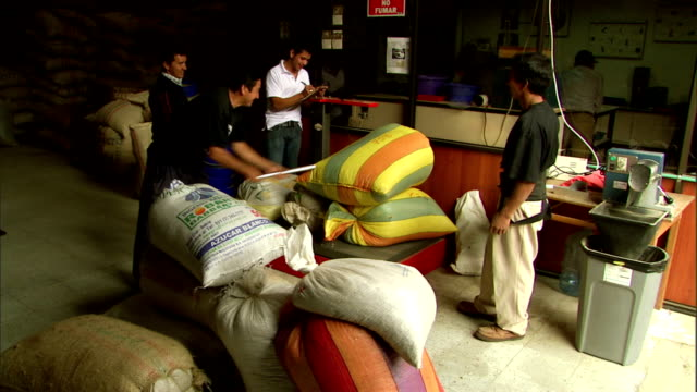 a supervisor examines coffee beans in bags. - 麻袋点の映像素材/bロール