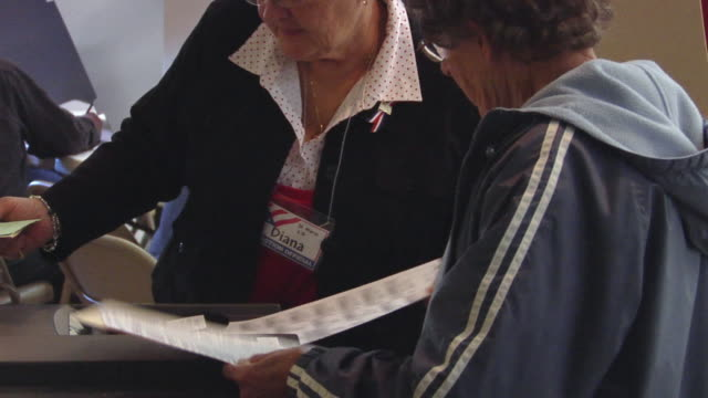 MS, ZO, Supervisor helping woman inserting voting ballot into electronic voting machine, St. Marys, Ohio, USA, DEFOCUS