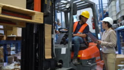 Supervisor instructing delivery schedule to forklift driver