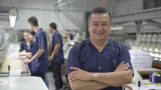 stockvideo's en b-roll-footage met toezichthouder kijken naar de camera en de marktdeelnemers die werken achter - latijns amerikaanse en hispanic etniciteiten