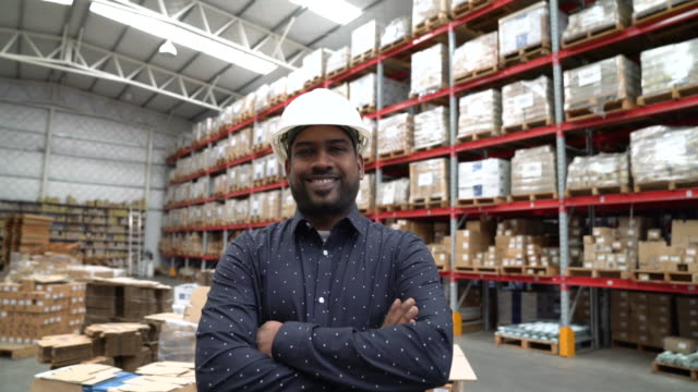 Supervisor smiling with arms crossed in warehouse