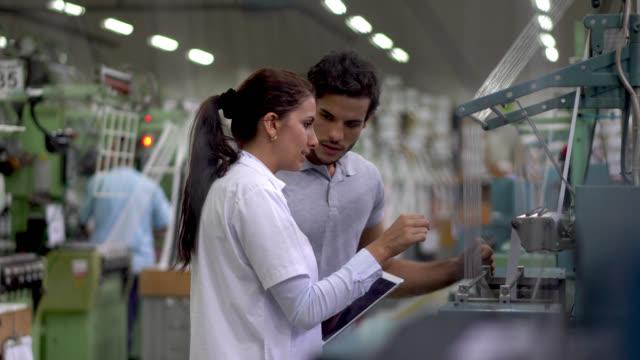 粘着テープ工場での生産ライン中に機械オペレーターと話すスーパーバイザー - 絆創膏点の映像素材/bロール