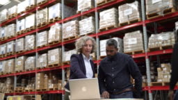 Supervisors discussing over laptop in warehouse