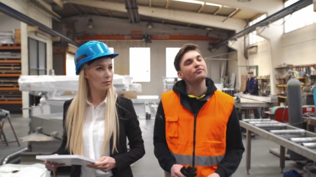 Supervisors with clipboard walking and talking on platform in factory