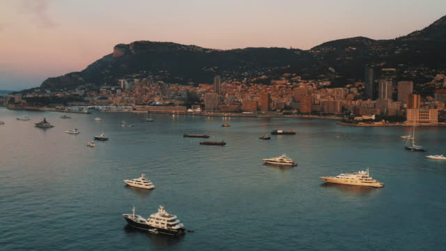 super-yachts moored in the bay at sunset filmed by drone during the monaco yacht show 2019 - monaco stock videos & royalty-free footage