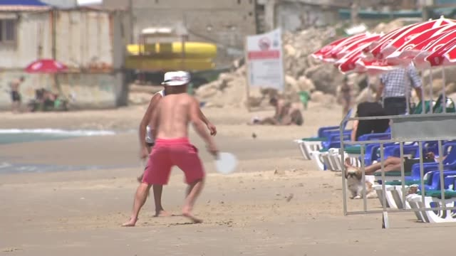 Support in Israel for Gaza military operation Tel Aviv DAY Wide shot of sun loungers on beach Person sitting on sun lounger on beach and man...