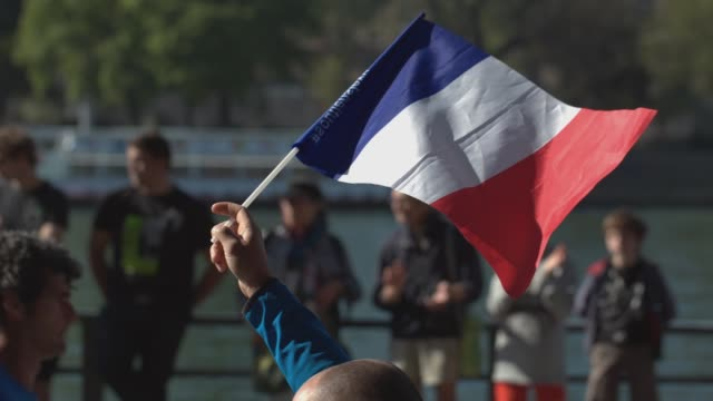 Supporter holding the french national flag and runners in the background during the sport event Paris Marathon 2017