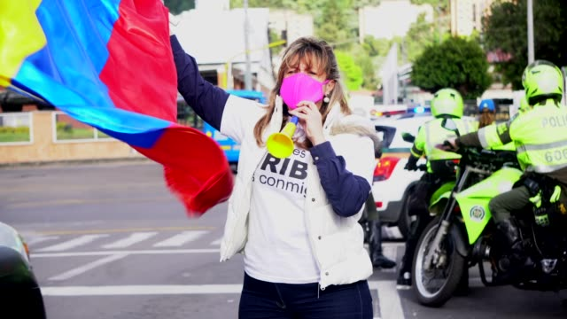 supporter of former president álvaro uribe velez blows a horn and holds a flag as cars go by honking their horns on august 7 in bogotá, colombia. the... - veicolo di terra per uso personale video stock e b–roll