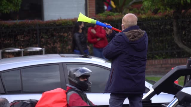 supporter of former president álvaro uribe velez blows a horn as cars go by on august 7 in bogotá, colombia. the supreme court made the decision to... - veicolo di terra per uso personale video stock e b–roll