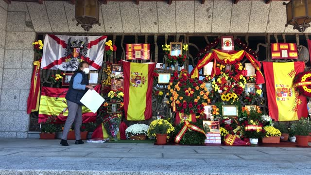 stockvideo's en b-roll-footage met supporter of francisco franco picks up a calendar outside the pantheon containing franco's tomb at el pardo mingorrubio cemetery during the 45th... - pardo