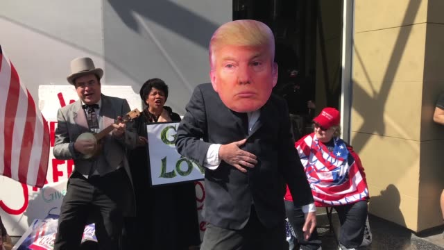 A supporter of President Donald Trump wears a mask of the president as he dances near Trump's star on the Hollywood Walk of Fame in Los Angeles...