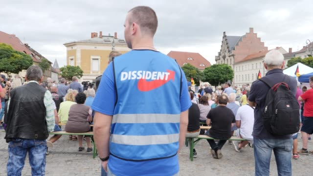 a supporter of the rightwing alternative for germany attends an election campaign is wearing a shirt with the inscription dissident and is listening... - engraved image stock videos and b-roll footage