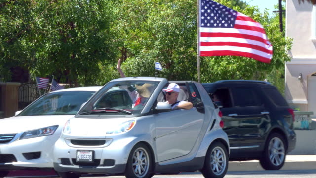 supporters in cars with american flag driving in los angeles, california, 4k - political rally stock videos & royalty-free footage