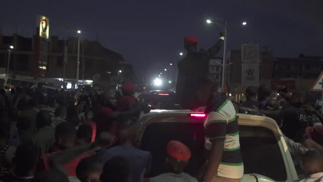 supporters of bobi wine, challenger in uganda's presidential election, follow his car at night time political rally, kampala - kampala stock videos & royalty-free footage
