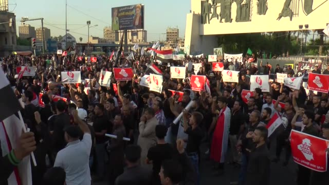 supporters of shiite cleric muqtada alsadr hold banners during a demonstration against government as they demand reform at tahrir square in baghdad... - muqtada al sadr video stock e b–roll
