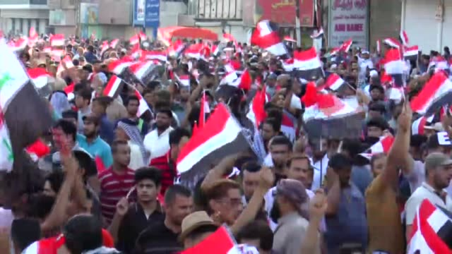 supporters of shiite cleric muqtada alsadr hold flags and chant slogans during a demonstration demanding political reform at tahrir square in baghdad... - muqtada al sadr stock videos & royalty-free footage