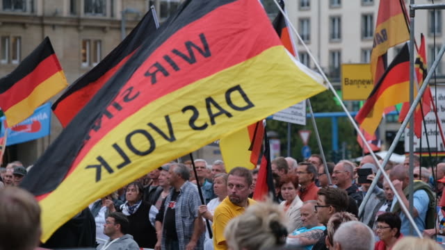"""supporters of the anti-muslim pegida movement, including one waving a german flag that reads: """"wir sind das volk"""" , gather following their 187th... - dresden germany stock videos & royalty-free footage"""