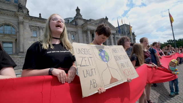 supporters of the friday for future climate change awareness movement including one holding a sign that reads 2038 is too late in reference to the... - wachsamkeit stock-videos und b-roll-filmmaterial