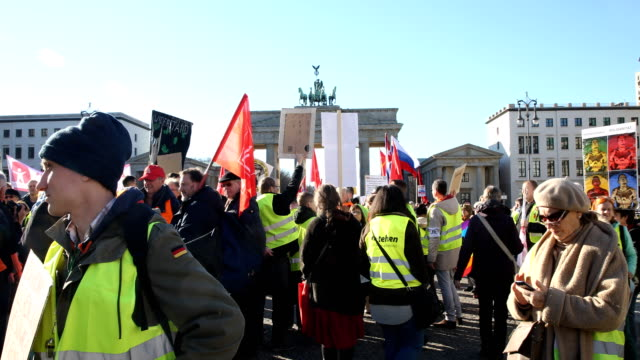 """supporters of the new left-wing """"stand up"""" movement gather at a demonstration which started at potsdamer platz and ended here at the brandenburg gate... - links platz stock-videos und b-roll-filmmaterial"""