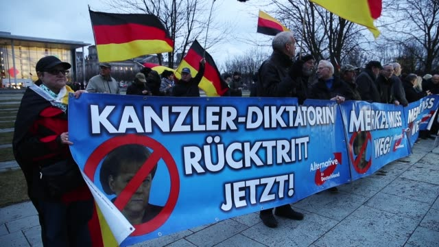 Supporters of the rightwing Alternative for Germany political party hold German flags and a banner that reads 'ChancellorDictator Resignation Now' in...