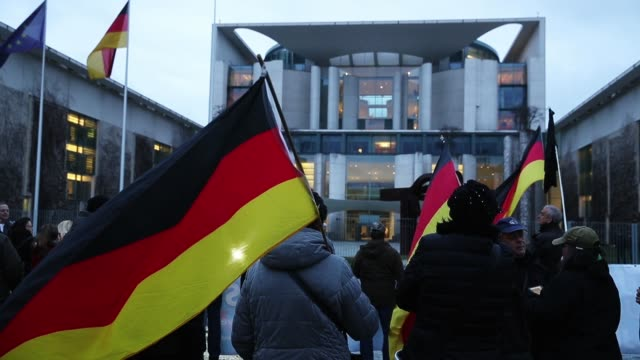 Supporters of the rightwing Alternative for Germany political party hold German flags as they gather to protest against German Chancellor Angela...