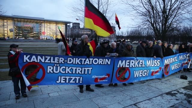 Supporters of the rightwing Alternative for Germany political party hold German flags and a banner that shows a crossedout German Chancellor Angela...